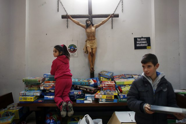 A girl reacts as she is asked not to step on the table as she chooses games during the distribution of donated toys to low income families at a church in Madrid January 5, 2015. Traditionally, children in Spain receive their presents delivered by the Three Wise Men on the morning of January 6 during the Christian holiday of the Epiphany. (Photo by Susana Vera/Reuters)