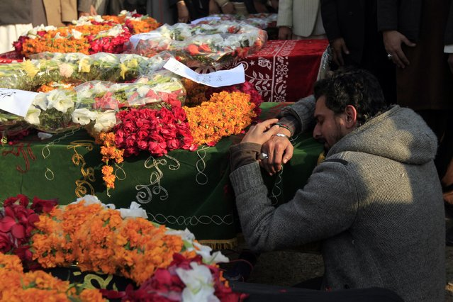 A man mourns over the casket of his relative who was killed in a suicide attack before his funeral in Rawalpindi January 10, 2015. (Photo by Faisal Mahmood/Reuters)