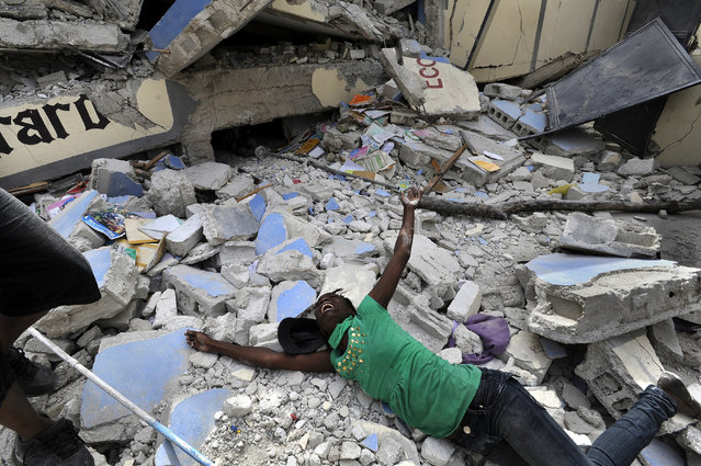 """In this January 2010 photo submitted by the Washington Post tilted """"Shattered Lives"""", Cindy Tersme throws herself amid the rubble of Ecole St. Gerard, screaming in anguish as she searches for her brother Jean Gaelle Dersmorne, 14,  in Haiti. (Photo by Carol Guzy/AP Photo/The Washington Post)"""