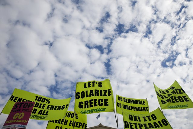 Protesters raise their placards as a Greek national flag flutters atop the parliament building during a rally held ahead of the 2015 Paris Climate Change Conference, known as the COP21 summit, in Athens, Greece, November 29, 2015. (Photo by Alkis Konstantinidis/Reuters)