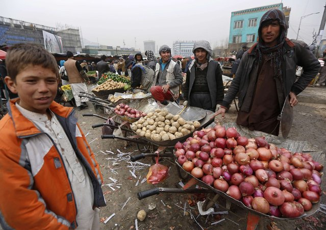 Afghans sell onions and potatoes along a street in Kabul January 12, 2015. (Photo by Omar Sobhani/Reuters)
