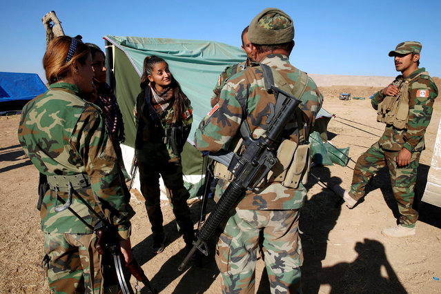 Iranian-Kurdish female fighters talk to Peshmerga forces during a battle with Islamic State militants in Bashiqa, near Mosul, Iraq November 3, 2016. (Photo by Ahmed Jadallah/Reuters)