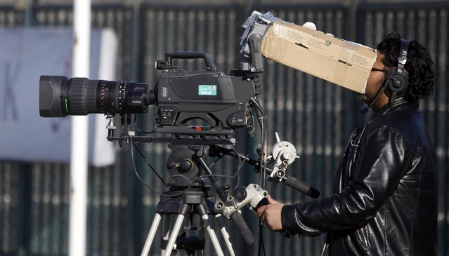 A cameraman uses cardboard to cover his viewfinder during cold weather at the Egyptian Premier League soccer match between Al Ahly and Al Masry at El-Gouna stadium in Hurghada January 10, 2015. (Photo by Amr Abdallah Dalsh/Reuters)
