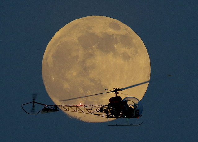 The moon is seen in its waxing gibbous stage as it rises behind the helicopter from the original Batman television show, which people can ride at the New Jersey State Fair, Saturday, June 22, 2013, in East Rutherford, N.J. The moon, which will reach its full stage on Sunday, is expected to be 13.5 percent closer to earth during a phenomenon known as supermoon. (Photo by Julio Cortez/AP Photo)