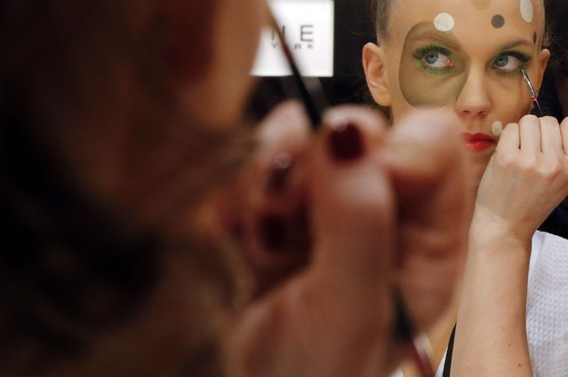 A model has her makeup done backstage before she presents a makeup creation during a show by Maybelline New York at the Berlin Fashion Week Autumn/Winter 2015 in Berlin January 19, 2015. (Photo by Fabrizio Bensch/Reuters)