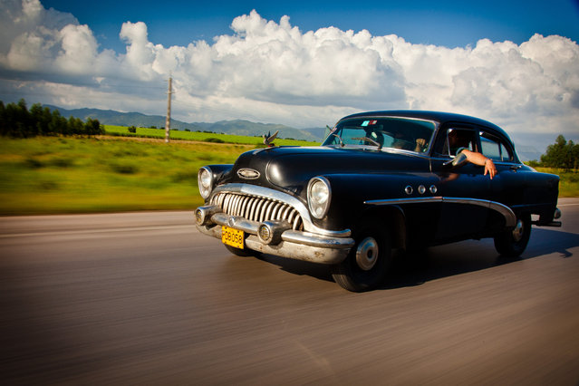 """Cruising in Cuba"". The National Highway in Cuba has many stretches where you will not see another car for miles. Then when you do see one, it is an old classic like this 1950's Buick which looks at home on the open road with the Cuban landscape of fields and mountains in the distance. (Photo and caption by James Kao/National Geographic Traveler Photo Contest)"