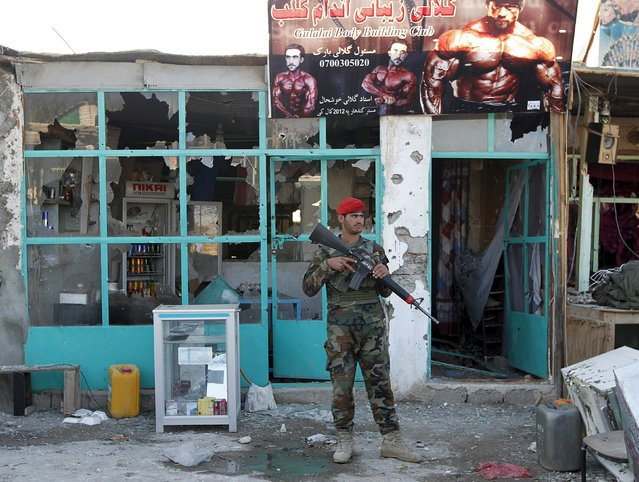 Afghan National Army (ANA) soldiers stand guard in front of a shop burned during the Taliban attack on Kandahar Airport in Kandahar, December 9, 2015. (Photo by Reuters/Stringer)