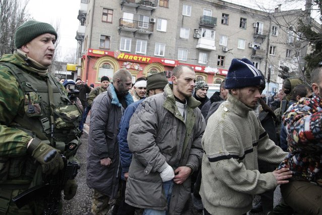 Prisoners of war (POWs) from the Ukrainian armed forces, are escorted by members of the armed forces of the separatist self-proclaimed Donetsk People's Republic, as they visit a public transport stop, where civilians were earlier killed on Thursday, in Donetsk, January 22, 2015. (Photo by Alexander Ermochenko/Reuters)