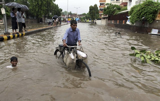An Indian child swims beside a man pushing his cycle past a flooded road after heavy rain lashed the city in Ahmadabad, India, Thursday, July 4, 2013. (Photo by Ajit Solanki/AP Photo)