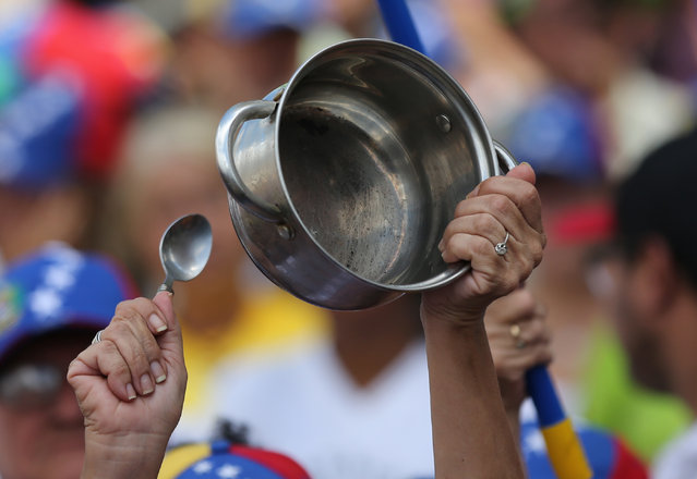 "A woman bangs on an empty pot during an event billed as the ""March of the empty pots"", in Caracas, Venezuela, Saturday, January 24, 2015. Thousands of opponents of President Nicolas Maduro marched in the capital Saturday to denounce the socialist government for a deepening economic crisis marked by widespread shortages and galloping inflation. (Photo by Ariana Cubillos/AP Photo)"
