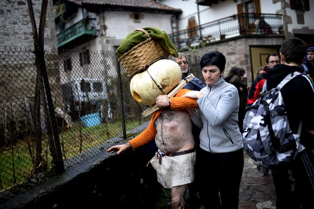A man wearing a pumpkin on his head is helped after falling over during carnival celebrations in Zubieta January 27, 2015. (Photo by Vincent West/Reuters)