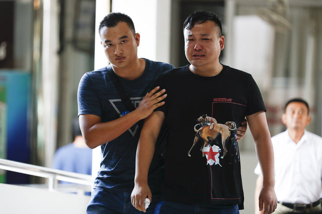 A Chinese relative of a victim in the recent boat sinking is consoled at the Vachira Phuket Hospital in Phuket, Thailand, Sunday, July 8, 2018. from Chalong pier in Phuket, Thailand, Sunday, July 8, 2018. Thai authorities have begun operations to salvage a tour boat that sank in a storm off the southern resort island of Phuket, killing 41 people, as they search for another 14 missing tourists. (Photo by Vincent Thian/AP Photo)