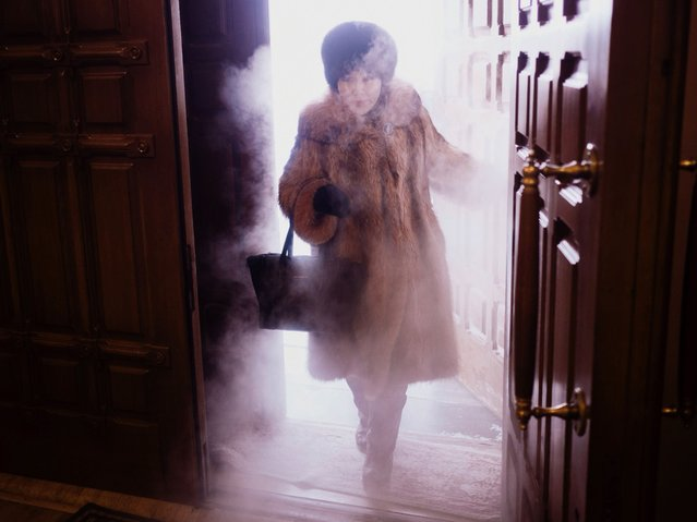 A local woman enters Preobrazhensky Cathedral in a swirl of freezing mist in the city of Yakutsk, Russia, considered to be the coldest city in the world, January 2014. (Photo by Amos Chapple/REX Features)