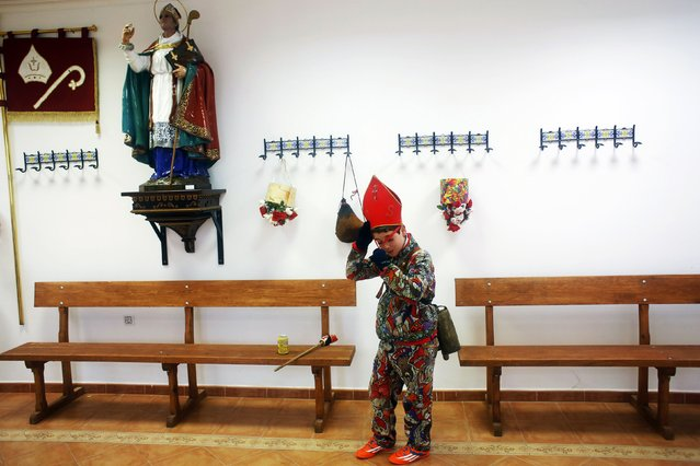 """A boy stands next to a statue of San Blas (Saint Blaise) as he dresses as a """"diablo"""" (devil) to parade around town during the """"Endiablada"""" festival in Almonacid del Marquesado, in central Spain February 3, 2015. (Photo by Susana Vera/Reuters)"""