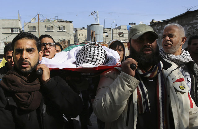 Palestinian relatives chant Islamic slogans as they carry the body of Hani Wahdan, 22, during his funeral in Gaza City, Saturday, December 26, 2015. (Photo by Adel Hana/AP Photo)