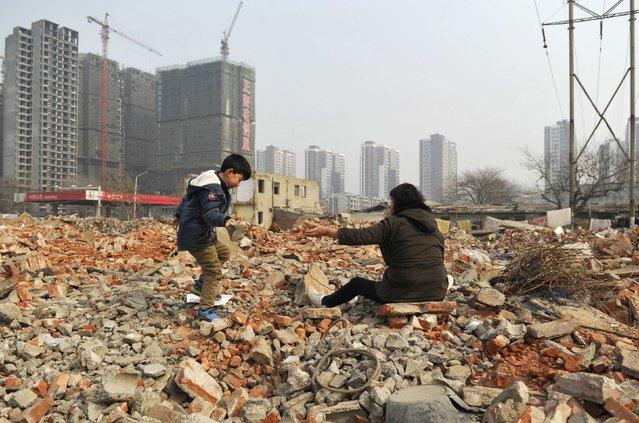 Primary school student Lele (L), 7, brings a piece of concrete to his grandmother as they look for recyclable steel bars at a demolition site in Zhengzhou, Henan province February 3, 2015. (Photo by Reuters/Stringer)