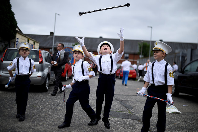 Young members of Loyalist Orders throw a baton in the air as they participate in Twelfth of July celebrations in Belfast, Northern Ireland July 12, 2018. (Photo by Clodagh Kilcoyne/Reuters)