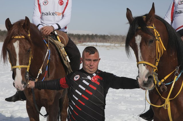 "Selcuk Davulcu, 31, a horse groom for the Dadas (Comrades) local sporting club, prepares the horses during a game of Cirit, a traditional Turkish equestrian sport that dates back to the martial horsemen who spearheaded the historical conquests of central Asia's Turkic tribes, between the Comrades and the Experts local sporting clubs, in Erzurum, eastern Turkey, Friday, March 5, 2021. The club officials said that Davulcu, a man with Down syndrome has been communicating with people just for the last four years thanks to the horses as they played a big role on his rehabilitation.The game that was developed more than a 1,000 years ago, revolves around a rider trying to spear his or her opponent with a ""javelin"" – these days, a rubber-tipped, 100 centimeter (40 inch) length of wood. A rider from each opposing team, which can number up to a dozen players, face each other, alternately acting as the thrower and the rider being chased. Cirit was popular within the Ottoman empire, before it was banned as in the early 19th century. (Photo by Kenan Asyali/AP Photo)"