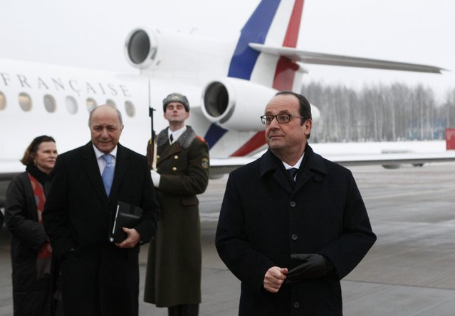 France's President Francois Hollande (R) and Foreign Minister Laurent Fabius (2nd L) take part in a welcoming ceremony upon their arrival at an airport near Minsk, February 11, 2015. (Photo by Valentyn Ogirenko/Reuters)
