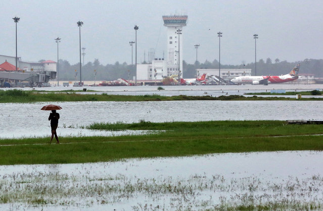 A man walks inside the flooded Cochin international airport after the opening of Idamalayar, Cheruthoni and Mullaperiyar dam shutters following heavy rain, on the outskirts of Kochi, India, August 15, 2018. (Photo by Sivaram V/Reuters)