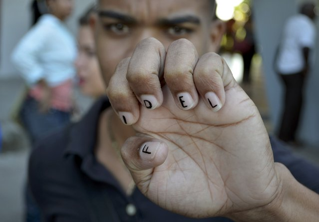 Leoanis, a student who is studying journalism, shows his marked fingernails as he pays tribute to Cuba's late President Fidel Castro in Santiago de Cuba, Cuba, November 28, 2016. (Photo by Alberto Reyes/Reuters)