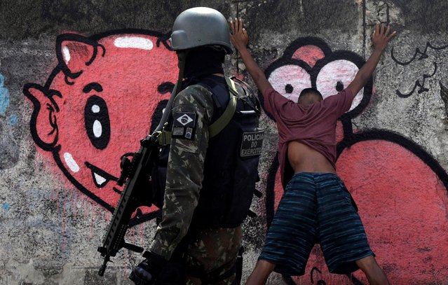 A Brazilian soldier strip searches youths during a patrol near Alemao slums complex in Rio de Janeiro, Brazil on August 22, 2018. (Photo by Ricardo Moraes/Reuters)