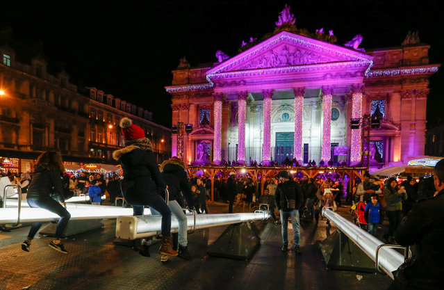 "Children ride on illuminated seesaws in front of the Brussels former stock exchange building La Bourse as part of the Christmas ""Winter Wonders"" (Plaisirs d'Hiver, Winter Pret) festivities, including a Christmas market and other events in central Brussels, Belgium, November 26, 2016. (Photo by Yves Herman/Reuters)"