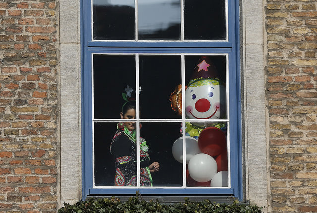 A reveler watches from a window the traditional Rose Monday carnival parade in Duesseldorf, Germany, Monday, February 16, 2015. (Photo by Frank Augstein/AP Photo)