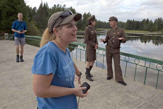In this Friday, August 17, 2018, photo, Sinead of Australia, center, and Tarjei Naess Skrede of Norway, left, stand near North Korean guides during a hiking trip organized by Roger Shepherd of Hike Korea, unseen, which included a tour of a monument near Mount Paektu in North Korea. (Photo by Ng Han Guan/AP Photo)