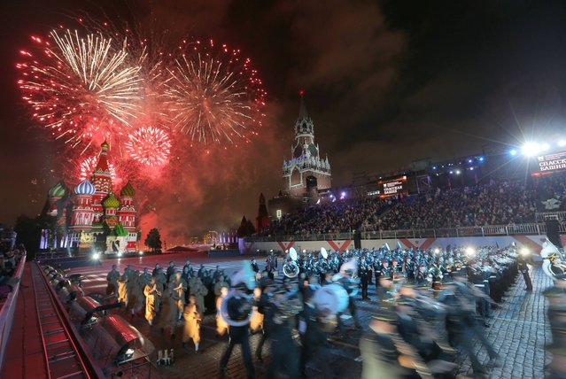 """Fireworks explode in the sky over St. Basil Cathedral during the """"Spasskaya Tower"""" International Military Orchestra Music Festival at the Red Square in Moscow, Russia, late Saturday, September 7, 2013. (Photo by Sergei Grits/AP Photo)"""
