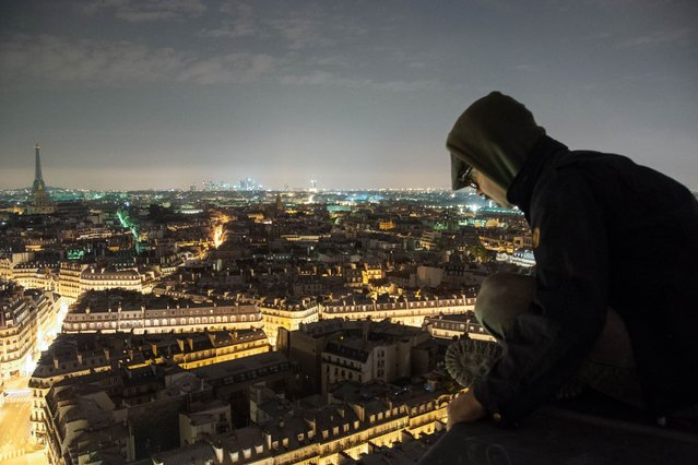 Urban explorer Bradley Garrett looks down at the streets of Paris from the roof of Saint-Sulpice church, in the Luxembourg Quarter of the VIe arrondissement, in Paris. (Photo by Bradley L. Garrett/Barcroft Media)