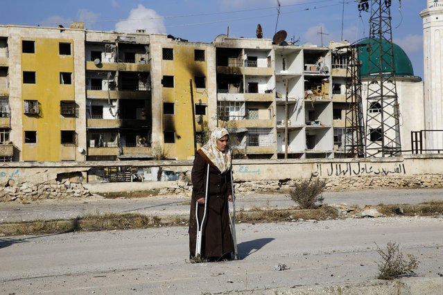 In this Sunday, December 4, 2016 photo, Nisrin Malaji returns to her looted home in the Hanano district of eastern Aleppo, Syria. It's a painful homecoming shared by hundreds of Syrians who are returning to areas devastated by years of war and then retaken from the city's embattled rebels in a recent government offensive. More than 30,000 people have fled Aleppo since the latest government offensive began last month, joining the more than 10 million Syrians – nearly half the population – who have fled their homes since the conflict began. (Photo by Hassan Ammar/AP Photo)