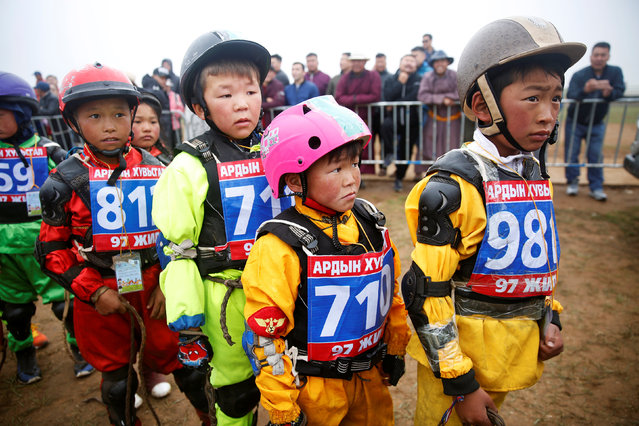 Child jockeys wait in line for a check up before a horse race at the Mongolian traditional Naadam festival, on the outskirts of Ulaanbaatar, Mongolia July 11, 2018. (Photo by Rentsendorj Bazarsukh/Reuters)