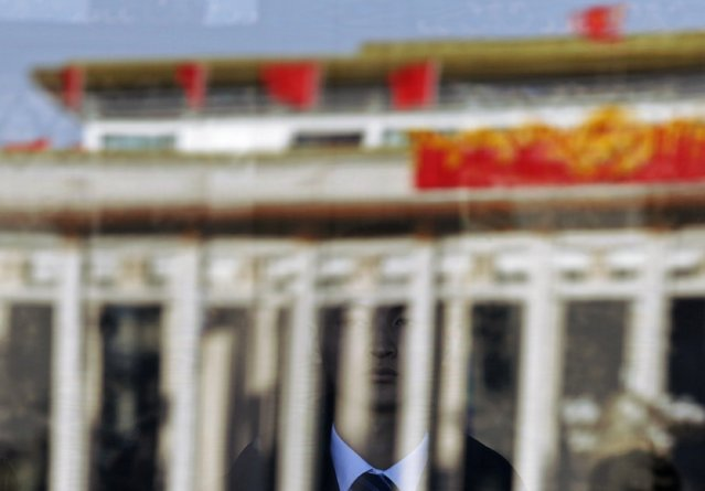 A security officer is reflected in a window at the Great Hall of the People during the opening session of the Chinese People's Political Consultative Conference (CPPCC) in Beijing, March 3, 2015.  REUTERS/Kim Kyung-Hoon