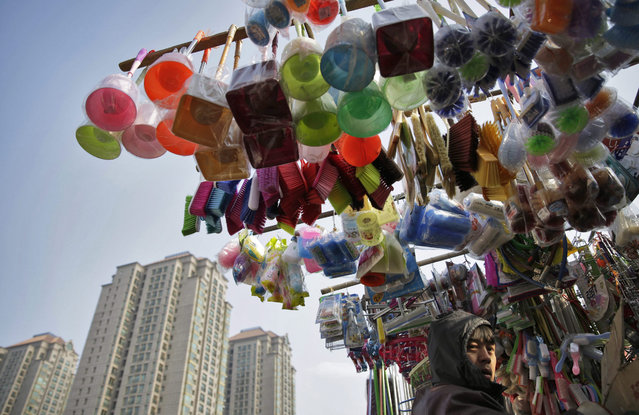 A Chinese stall vendor is seen with as household goods are hung on poles above his stall at a market in Beijing, China, 14 January 2016. China will announce its fourth-quarter and full-year 2015 economic growth data on 19 January amid continued concern over the slowing of the world's second-largest economy. (Photo by How Hwee Young/EPA)