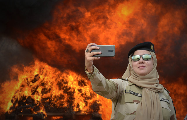 A member of the Pakistani Anti-Narcotic Force (ANF) takes a selfie beside a pile of burning drugs and liquor during a ceremony at the Kacha Ghari army firing range, on the outskirts of Peshawar on October 16, 2018, after the contraband was seized in raids across the province. (Photo by Abdul Majeed/AFP Photo)