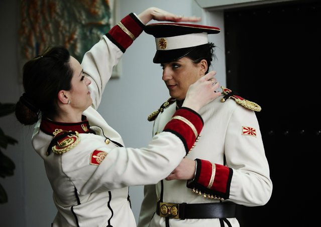 Corporal Dragana Kitanovska (L) adjusts the hat of her comrade Verica Zlatevska at an army barracks in Skopje March 4, 2015. Macedonia's honour army battalion, the ceremonial uniformed guard that receives every foreign president, dignitaries and delegations, but also sees off and welcomes the head of state every time he leaves the country, has a different glow. For the first time in the history of Macedonia's army, the honour guard has two women in its ranks. There has not been an event in which one of them is not in the first row. Zlatevska joined the army in 2003, Kitanovska in 2006. Picture taken March 4, 2015.  REUTERS/Ognen Teofilovski (MACEDONIA - Tags: MILITARY SOCIETY)