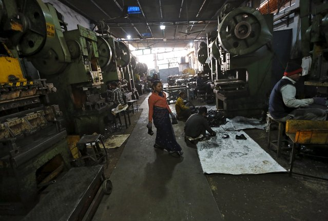 Workers make auto parts on machines inside a manufacturing unit in Faridabad, India, December 24, 2015. (Photo by Adnan Abidi/Reuters)