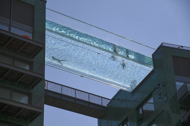 People swim in the Sky Pool, a transparent swimming pool bridge across two exclusive residential blocks standing next to the US Embassy in Nine Elms, in London, Tuesday, June 1, 2021. Britain sees temperatures increasing for the second day in a row after the mercury hit 25C (77 Fahrenheit) for the warmest day of the year so far on Bank Holiday Monday. (Photo by Alberto Pezzali/AP Photo)
