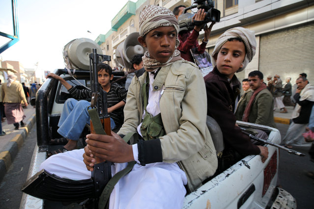 Boys who are part of the Houthi fighters, hold weapons as they ride on the back of a patrol truck  during a demonstration to show support to the movement, and rejecting foreign interference in Yemen's internal affairs, in Sanaa March 13, 2015. (Photo by Mohamed al-Sayaghi/Reuters)