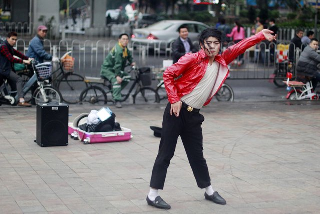 Pedestrians look on as an impersonator of late pop singer Michael Jackson dances near a street in Guangzhou, Guangdong province, March 18, 2015. (Photo by Alex Lee/Reuters)