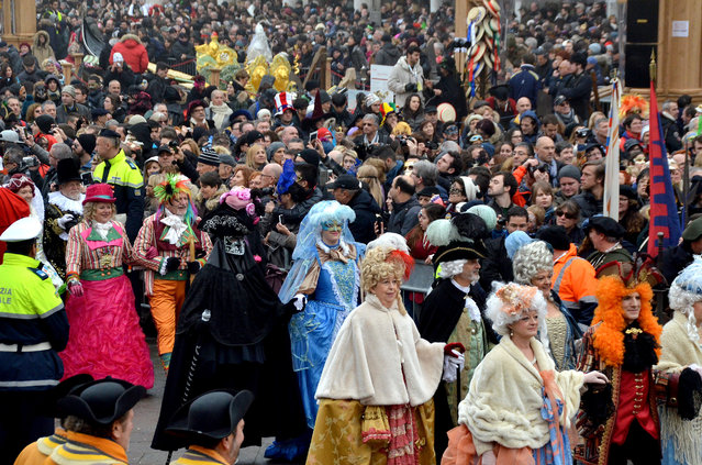People wearing costumes gather in St. Mark's Square in Venice, Italy, Sunday, January 31, 2016. (Photo by Luigi Costantini/AP Photo)
