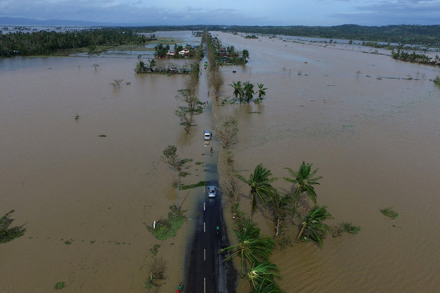 An aerial photo shows a flooded highway after typhoon Nock-Ten made landfall in Polangui, Albay province on December 26, 2016. Typhoon Nock-Ten, which made landfall on the eastern island province of Catanduanes on December 25, is forecast to move westward towards the country's heartland, packing winds of 215 kilometres (134 miles) per hour. (Photo by Charism Sayat/AFP Photo)