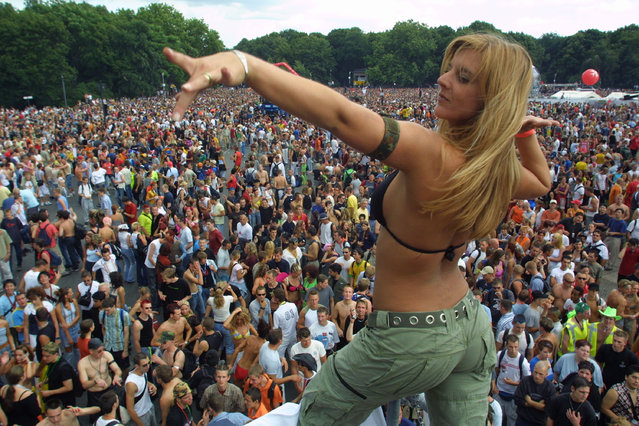 A woman dances on top of a truck blaring techno music to thousands of ravers during the annual Love Parade July 12, 2003 in Berlin, Germany. (Photo by Sean Gallup/Getty Images)