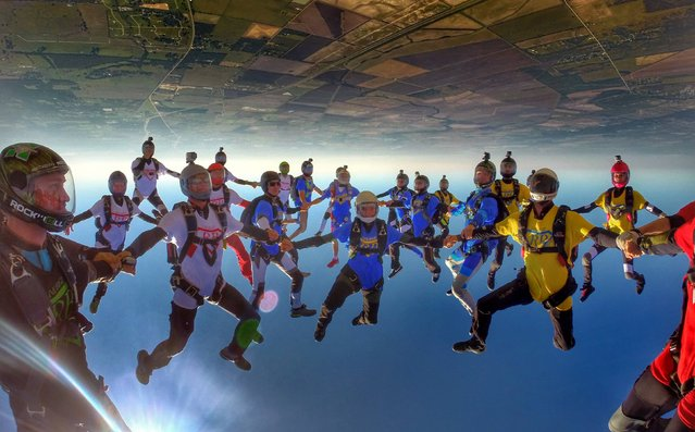 "This is the remarkable moment a group of skydivers performed a world record breaking feat in honour of their friend who died while skydiving. Known as a ""Bigway"", the daring jump involves 57 people holding hands in a predetermined design as they hurtle towards the ground, head first. (Photo by Ben Nelson/Caters News)"