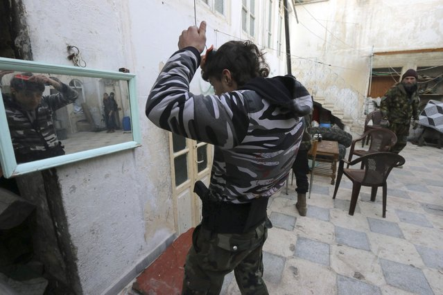 A Free Syrian Army fighter combs his hair in Old Aleppo January 1, 2015. (Photo by Abdalrhman Ismail/Reuters)