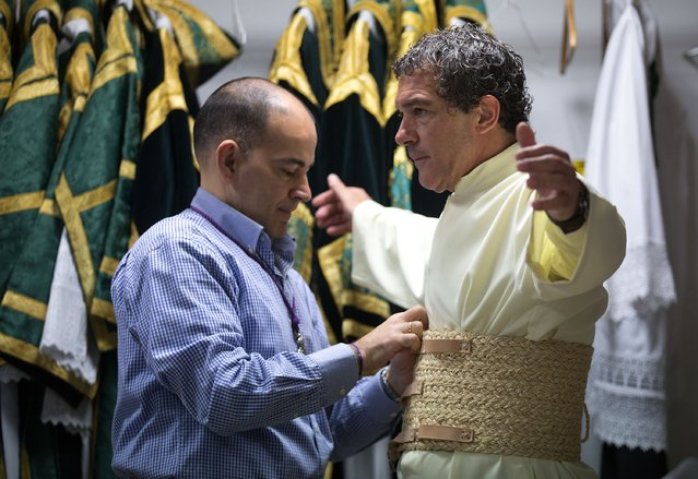 Antonio Banderas (R) is helped to dress as he attends the Maria Santisima de Lagrimas y Favores procession at San Juan Bautista church during Holy Week celebrations on March 29, 2015 in Malaga, Spain. (Photo by Gonzalo Arroyo Moreno/Getty Images)