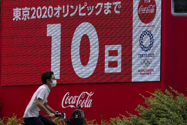 """A person on his bicycle wearing a protective mask passes by an electronic display that reads: """"10 days until Tokyo 2020 Olympics"""" Tuesday, July 13, 2021, in Tokyo. (Photo by Kiichiro Sato/AP Photo)"""