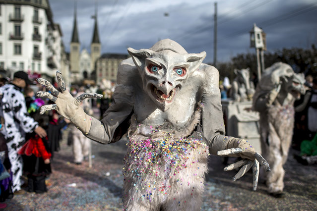 Masked revelers  parade through the streets during the start of the carnival  in Lucerne, Switzerland, Monday, February 8, 2016. (Photo by Alexandra Wey/Keystone via AP Photo)