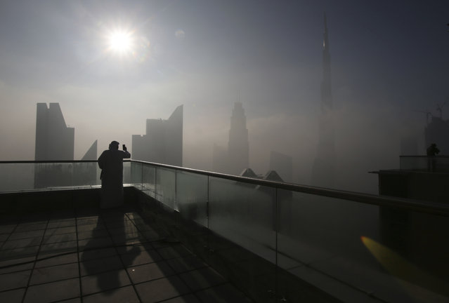 A man takes photos of the Burj Khalifa, world's tallest tower, on a foggy day in Dubai, United Arab Emirates, Friday, December 30, 2016. (Photo by Kamran Jebreili/AP Photo)